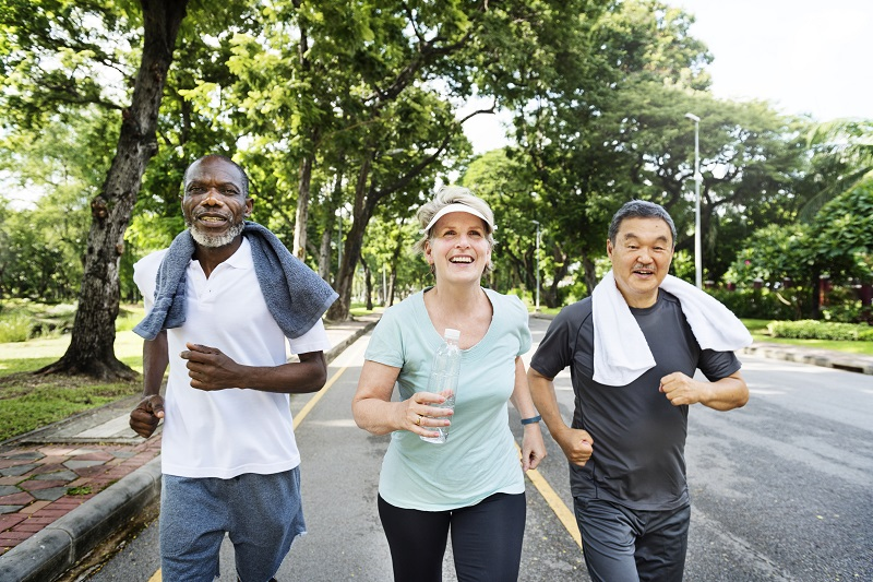 Over 50s staing healthy keeping fit - group of senior friends jogging together in a park